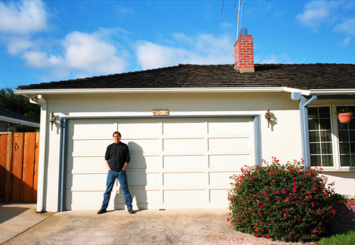 Steve Jobs stands in front of the Los Altos garage where he and Steve Wozniak co-founded Apple.